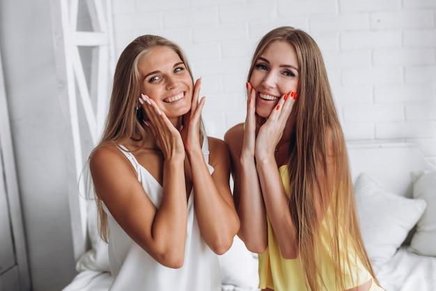 Sorrindo lindas garotas segurando as bochechas