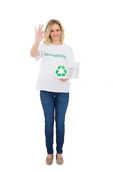 Sorrindo loira voluntário segurando a caixa de reciclagem, fazendo o gesto bem