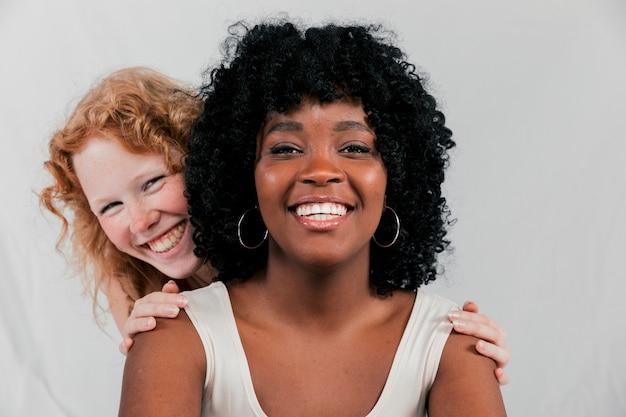 Sorrindo, loiro, mulher jovem, estar, atrás de, a, africano, amigo, contra, cinzento, fundo