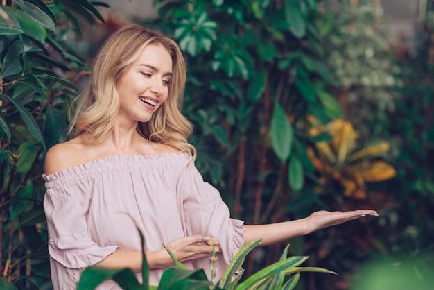 Sorrindo, loiro, mulher jovem, mostrando, palma aberta mão, ficar, perto, a, planta
