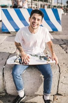 Sorrindo, macho, skateboarder, sentando, com, skateboard, frente, barricada