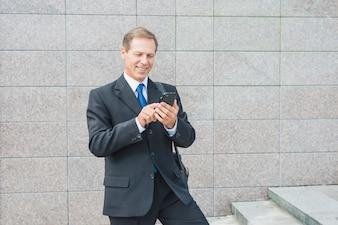 Sorrindo, maduras, homem negócios, usando, telefone móvel, em, ao ar livre