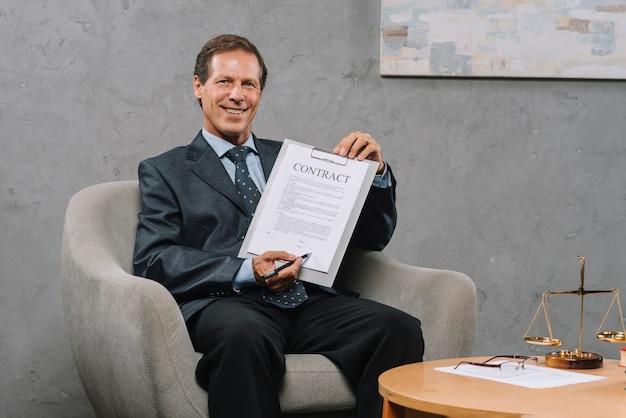 Sorrindo, maduro, advogado, pena segurando, apontar, assinatura, lugar, ligado, um, contrato, documento