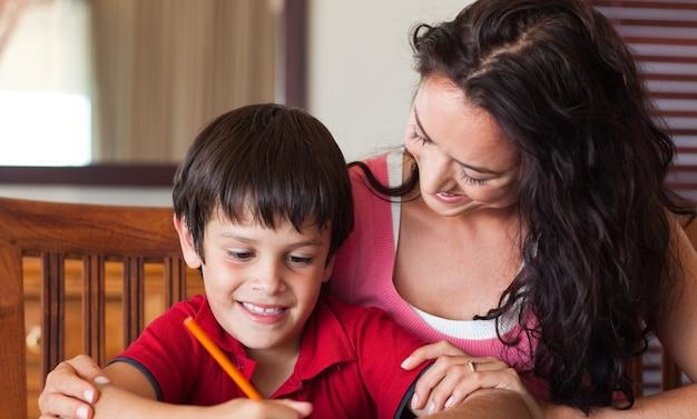 Sorrindo mãe ajudando seu filho a fazer a lição de casa