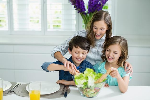 Sorrindo, mãe e crianças tigela de salada na cozinha