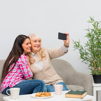 Sorrindo, mãe, e, dela, filha jovem, levando, selfie, ligado, telefone pilha, casa