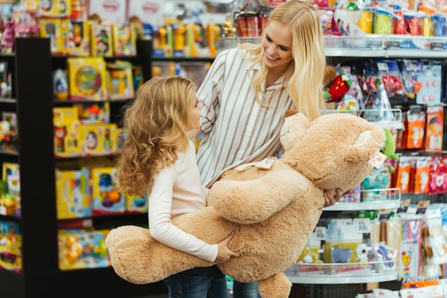 Sorrindo, mãe e filha em pé no supermercado