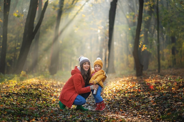 Sorrindo, mãe e filha em uma caminhada. dia de sol no parque outono