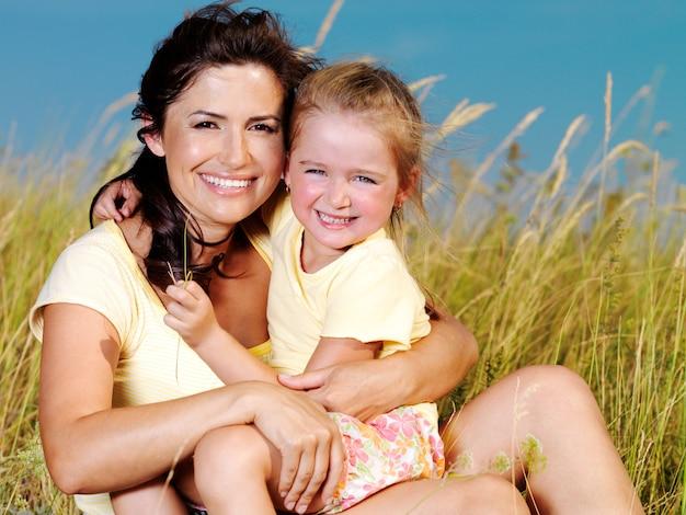 Sorrindo, mãe e filha na natureza.