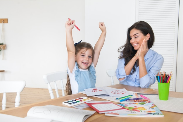 Sorrindo, mãe e filha se preparando para as aulas e desenha à mesa com lápis e tintas