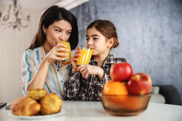 Sorrindo, mãe e filha sentada à mesa de jantar e tomando café da manhã saudável. eles estão bebendo suco de laranja.