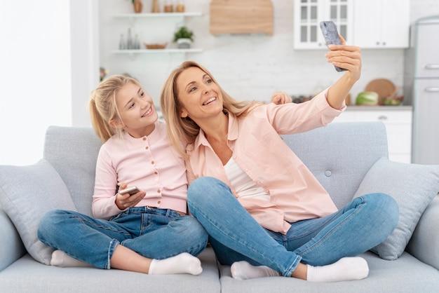 Sorrindo, mãe e filha tomando selfies