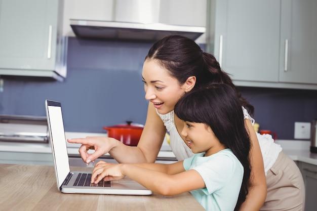 Sorrindo, mãe e filha usando um laptop