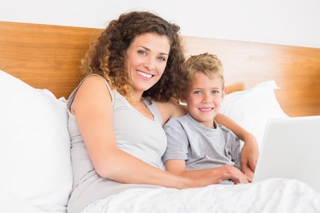 Sorrindo mãe e filho sentado na cama com laptop