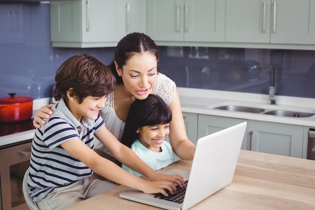 Sorrindo, mãe e filhos trabalhando no laptop