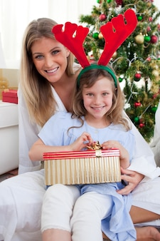 Sorrindo mãe e sua filha desembalando presentes de natal