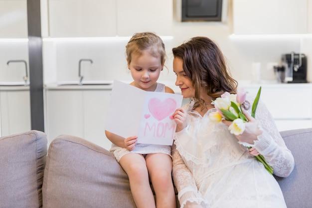 Sorrindo, mãe filha, leitura, cartão, sentando, ligado, sofá, com, segurando, buquê flor