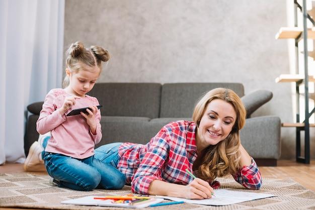 Sorrindo, mãe, livro desenho, com, dela, filha, usando, telefone móvel