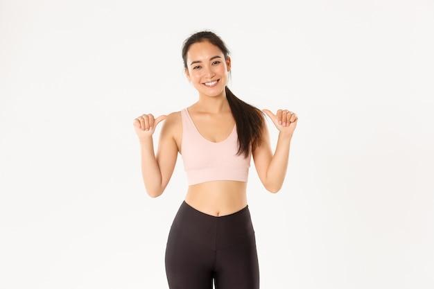 Sorrindo magro e forte, atraente preparador físico feminino asiático, instrutor pessoal ou treinador apontando para si mesma, o logotipo do ginásio, fundo branco.