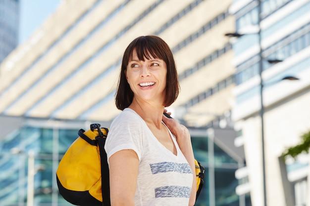 Sorrindo mais velho viajante carregando mochila na cidade