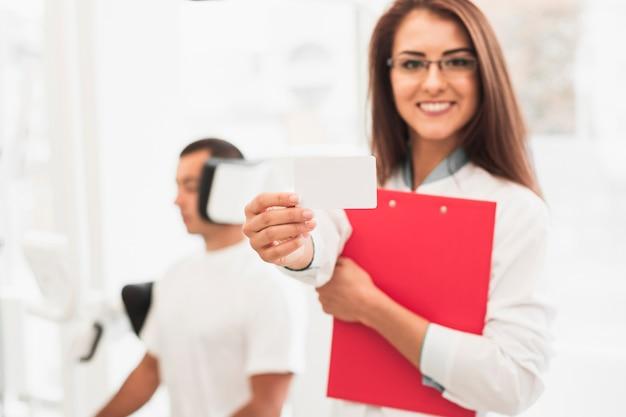 Sorrindo médica mostrando cartão simulado acima
