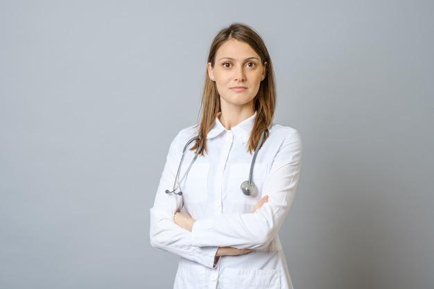 Sorrindo médica no jaleco com os braços cruzados