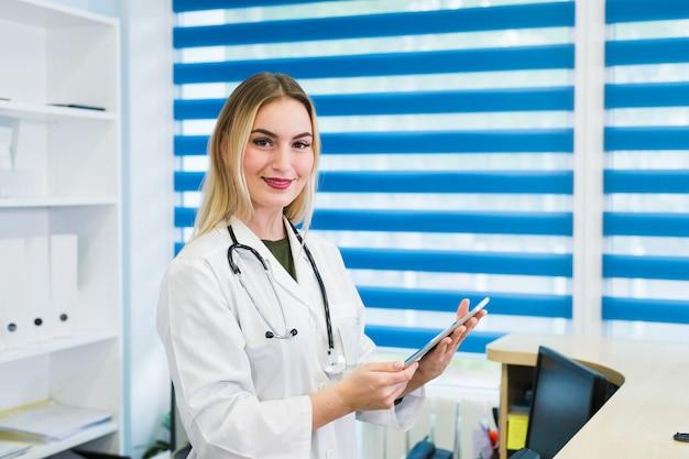 Sorrindo médica vestindo um uniforme e trabalhando na recepção do hospital, ela está escrevendo um relatório médico em uma prancheta e agendando compromissos
