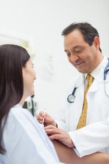 Sorrindo médico fazendo uma injeção para um paciente em uma sala de exame