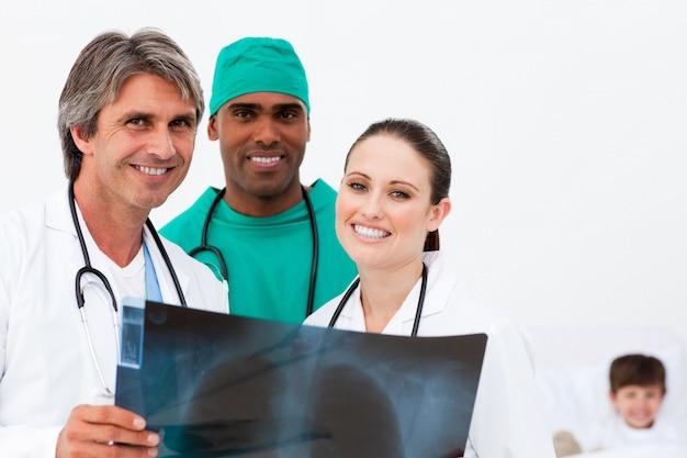 Sorrindo médicos examinando um raio-x e um menino na cama