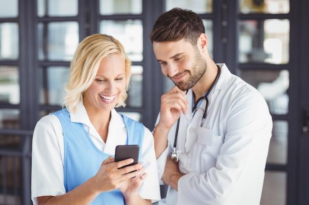 Sorrindo médicos usando telefone celular