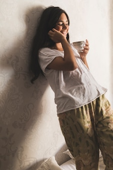 Sorrindo, menina adolescente, inclinar-se, papel parede, xícara segurando
