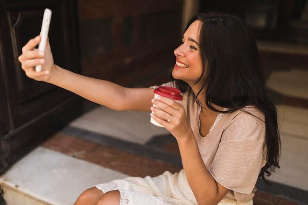 Sorrindo, menina adolescente, segurando, levar, café, copo, levando, selfie, de, telefone pilha