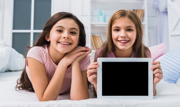 Sorrindo, menina, deitando, com, dela, amigo, cama, mostrando, em branco, tela, tablete digital