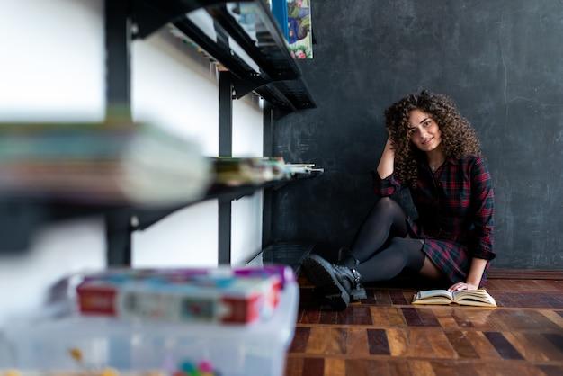 Sorrindo menina morena encaracolada com um livro sentado na biblioteca no chão e olhando para a câmera