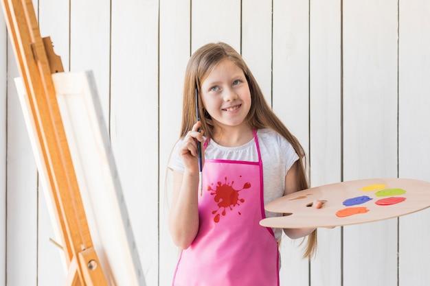 Sorrindo menina pensativa segurando a paleta e pincel em pé perto do cavalete