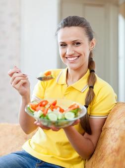 Sorrindo menina saudável comendo salada vegetariana