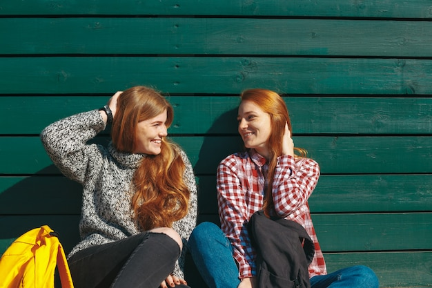 Sorrindo meninas conversando e brincando com o cabelo