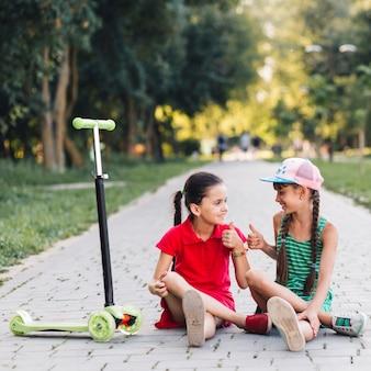Sorrindo, meninas, mostrando, polegar cima, sinal, para, um ao outro, ligado, passagem