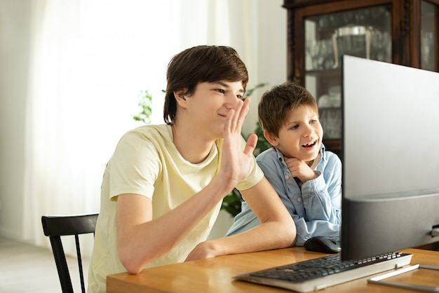 Sorrindo, menino e adolescente conversando on-line e acenando para a tela do computador.