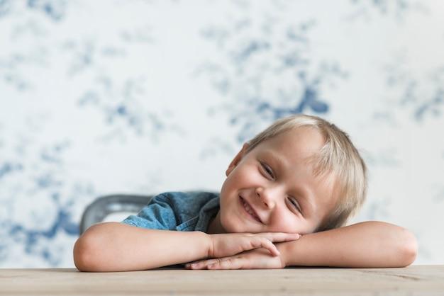 Sorrindo menino inclinando a cabeça na mão sobre a mesa de madeira