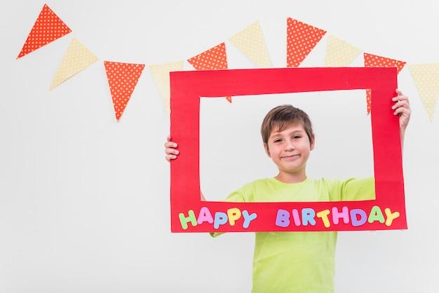 Sorrindo, menino, segurando, quadro, com, feliz aniversário, armação, contra, parede, decorado, com, bunting