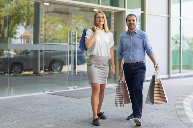 Sorrindo, middle-aged, par, shopping, carregar, sacolas papel, e, andar, ligado, rua cidade