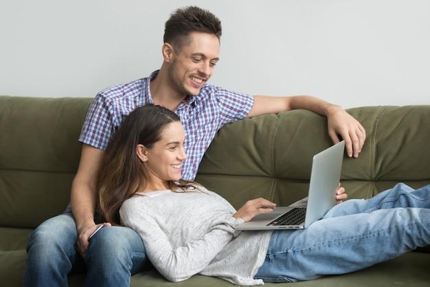 Sorrindo, millennial, par, desfrutando, usando computador portátil, relaxante, ligado, sofá, junto