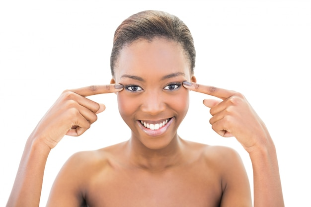 Sorrindo modelo bonito apontando para os olhos dela