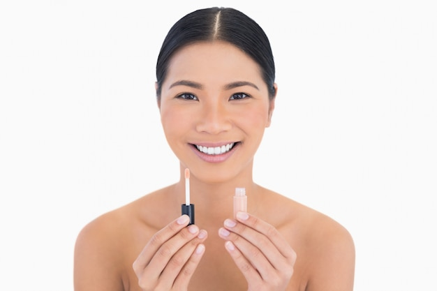 Sorrindo modelo bonito segurando brilho labial