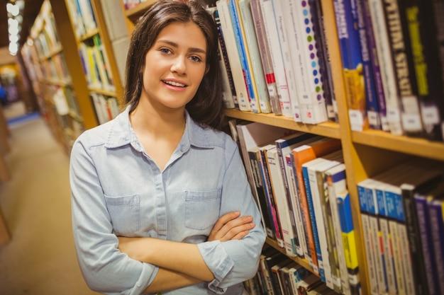 Sorrindo, morena, estudante, ficar, perto, bookshelves, com, braços cruzaram, em, biblioteca