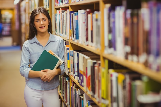 Sorrindo, morena, estudante, ficar, perto, bookshelves, enquanto, segurando, livros, em, biblioteca