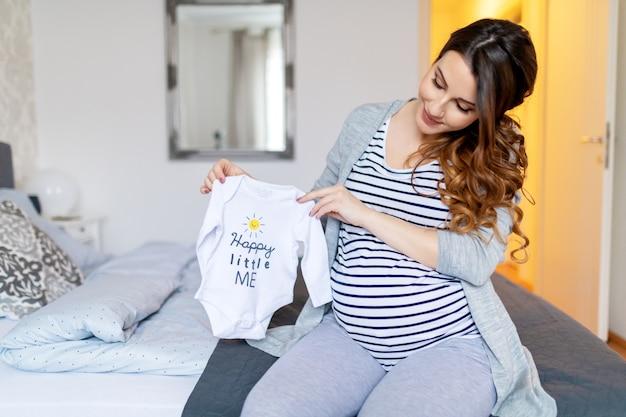 Sorrindo morena grávida com cabelos longos, na blusa de listra, segurando a roupa do bebê e sentado na cama no quarto.