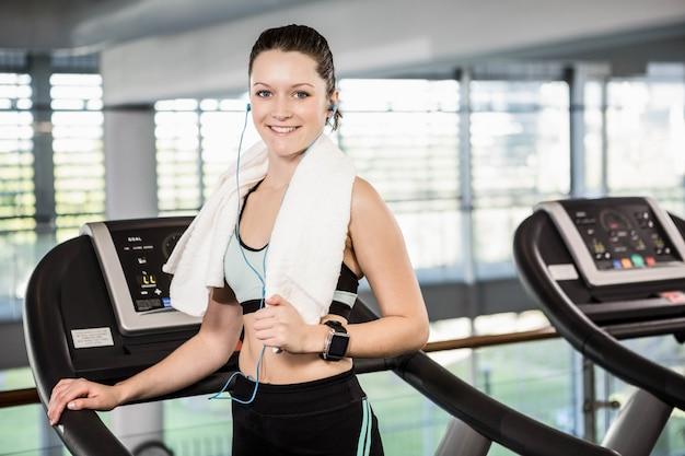 Sorrindo, morena, ligado, treadmill, olhando câmera, em, a, ginásio