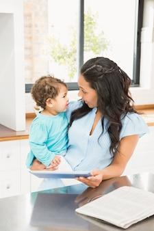 Sorrindo, morena, segurando, dela, bebê, e, usando, tabuleta, cozinha